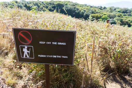 stay at the course: Keep off the grass please stay on the trail sign