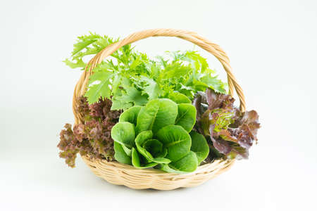 Composition with raw vegetables for salad and wicker basket isolated on white background