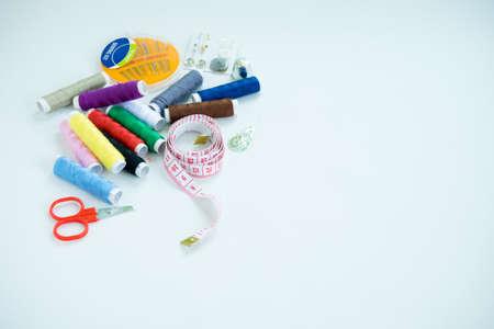 裁縫アクセサリー、ツール、カラフルなスプール、針、tapeof を測定ハサミ上面白い背景で隔離スレッドします。 写真素材