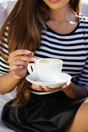 Young woman drinking coffee  in a cafe outdoors. Summer time photo