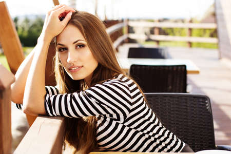 Young woman drinking coffee in a cafe outdoors photo