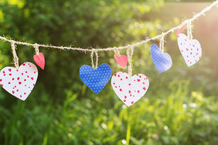 Colorful textured hearts hanging on green grass background photo