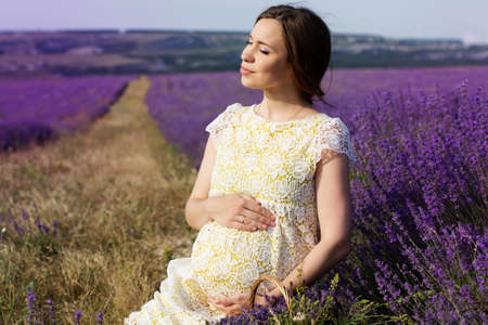 Beautiful pregnant woman in the lavender field Standard-Bild