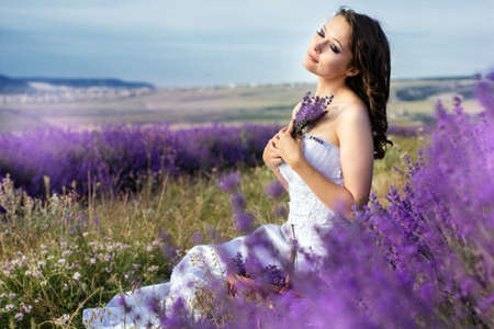 Beautiful bride posing at field of lavender photo