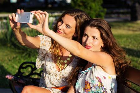 Two friends taking selfie by smartphone