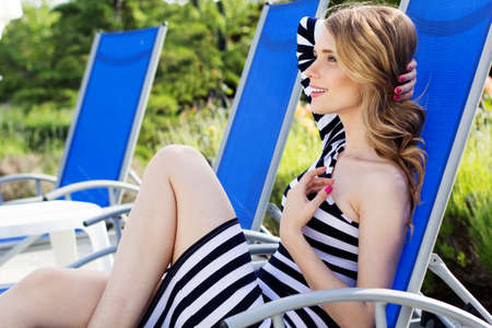 Beautiful woman is resting on the deck chair photo