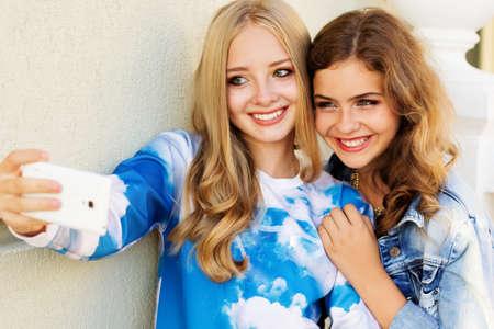 Two friends taking selfie by smartphone photo