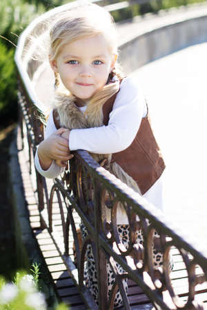 Little girl is sitting on the bench, autumn time Stockfoto