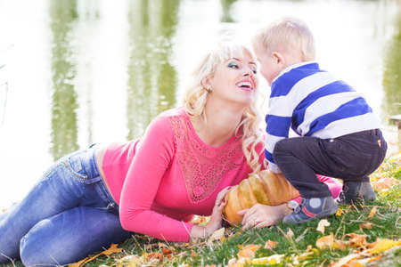 Mother and son near lake with pumpkin, autumn time photo