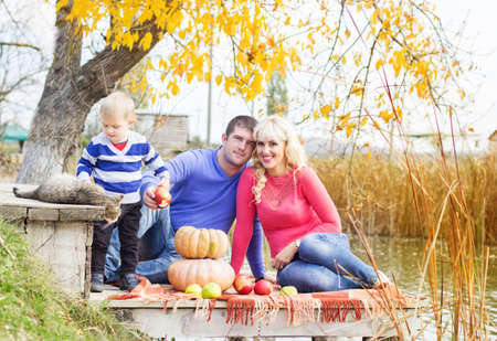 Young family near lake with pumpkins, autumn time photo