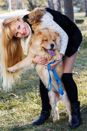 Attractive girl with her dog wearing warm clothes photo