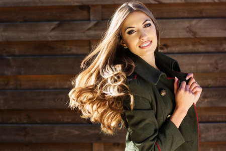 Young fashion girl near wooden wall photo
