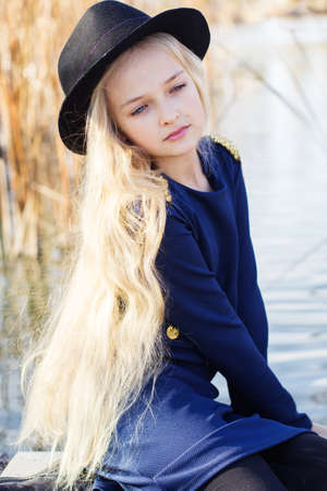 Little cute smiling girl with blonde hair outdoors is sitting near lake and wearing fashion dress. Portrait caucasian female blonde child model outside