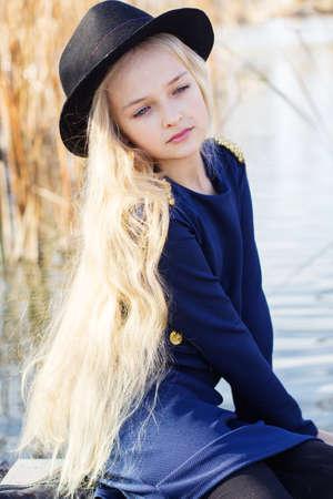 Muchacha sonriente linda con el pelo rubio al aire libre está sentado cerca del lago y con vestido de moda. Retrato modelo rubio niño caucásica femenina fuera Foto de archivo