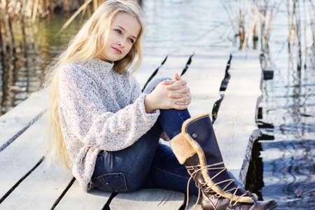 La niña linda está sentado al aire libre cerca del lago y con vestido de moda. Retrato modelo rubio niño caucásica femenina fuera