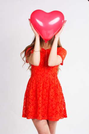 simbolo de la mujer: Mujer que sostiene el globo rojo del coraz�n Foto de archivo