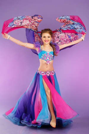 Beautiful belly dancer wearing a purple costume