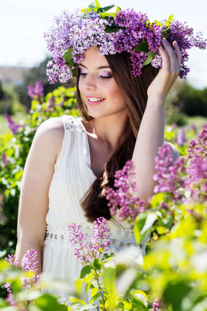Beautiful smiling girl is wearing beautiful wreath of lilac flowers photo
