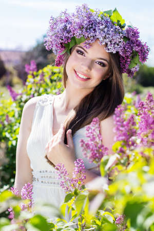 Beautiful smiling teenager girl is wearing beautiful wreath of lilac flowers Stockfoto