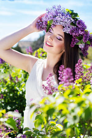 Beautiful smiling girl is wearing beautiful wreath of lilac flowers in spring garden Standard-Bild