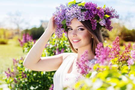 아름 다운 미소 소녀 라일락 꽃의 아름 다운 안주를 입고있다