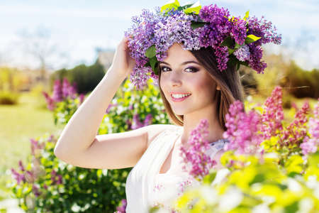 Beautiful smiling girl is wearing beautiful wreath of lilac flowers Stockfoto