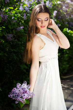 Beautiful smiling girl is wearing white dress with a lilac flowers photo