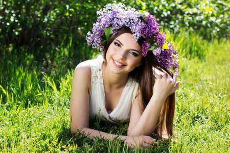 Beautiful smiling girl lying on green grass with fashion makeup is wearing beautiful wreath of lilac flowers photo