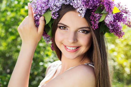 woman dress: Close up portrait of beautiful smiling girl with fashion makeup is wearing beautiful wreath of lilac flowers Stock Photo