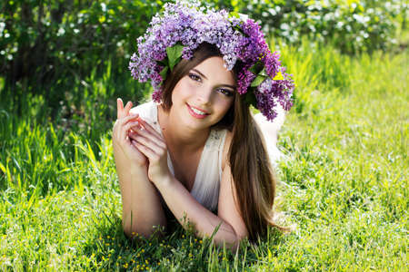 Beautiful smiling teen girl is lying on grass with fashion makeup is wearing beautiful wreath of lilac flowers photo
