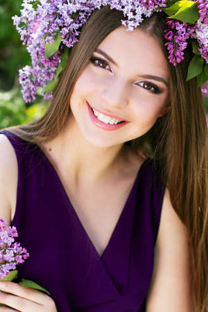 Beautiful smiling girl with fashion makeup is wearing beautiful nice dress and wreath of lilac flowers