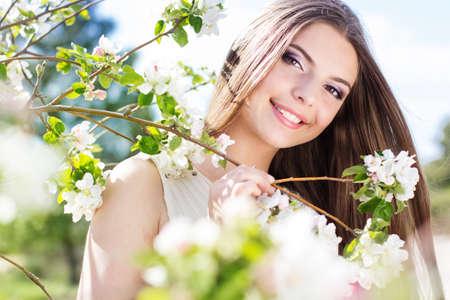 Happy girl near blossom cherry tree in spring garden