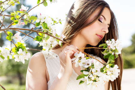 Portrait of beautiful smiling pretty teenager girl near blossom cherry tree brunch  in spring garden Standard-Bild