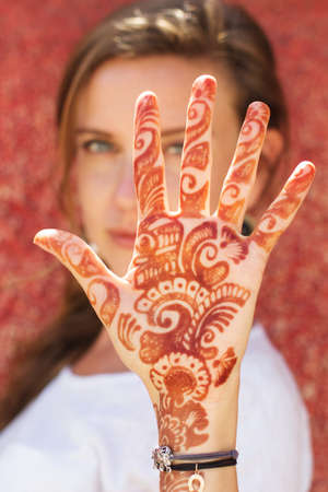 Mehendi art or Heena Tattoo on the hand of beautiful girl, India