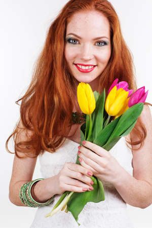 Beautiful redheaded girl with colorful tulips