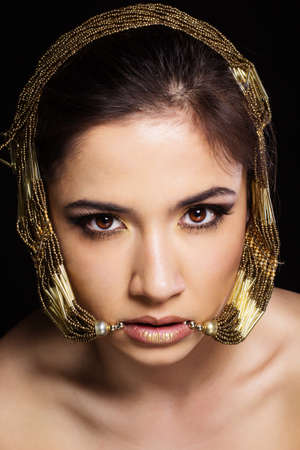 Pretty fashion woman with golden bijouterie in her mouth. Fashion photo. Beauty and style photo