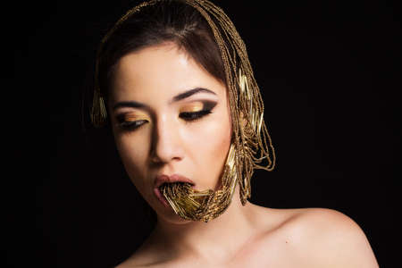 Pretty fashion girl with golden bijouterie in her mouth. Fashion photo. Beauty and style photo