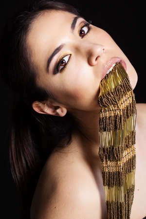 Pretty girl with golden bijouterie in her mouth. Fashion photo. Beauty and style photo