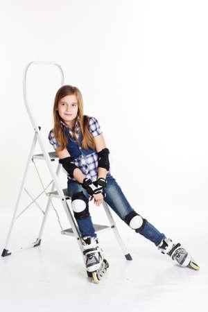 rollerskating: Cute child girl having fun in roller skates on a white background, studio shoot Stock Photo