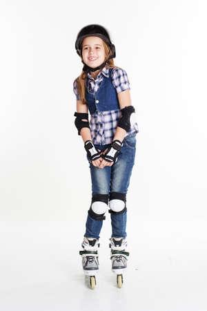 roller blade: Cute pretty child girl having fun in roller skates on a white background, studio shoot Stock Photo
