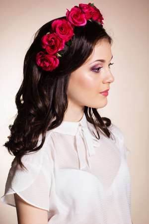 Fashion portrait of happy pretty brunette teenager girl is wearing white blouse and red roses wreath on her head photo