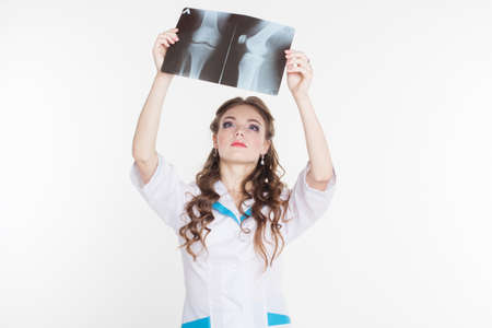 Young beautiful girl intern looking at the x-ray picture of knee isolated on white photo