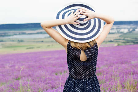 field stripped: Beautiful blonde girl is wearing stripped hat in fairy field of lavender. Summer timr