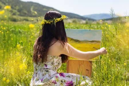 Young artist painting an floral landscape, summer time Stockfoto