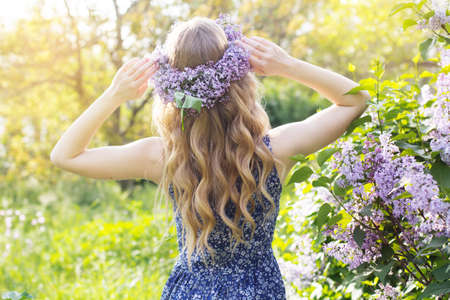 Girl with wreath from lilac purple flowers in green park, spring time Stockfoto
