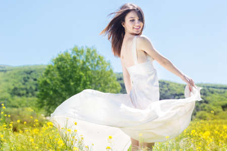 Beautiful girl in the yellow field is wearing flying white dress
