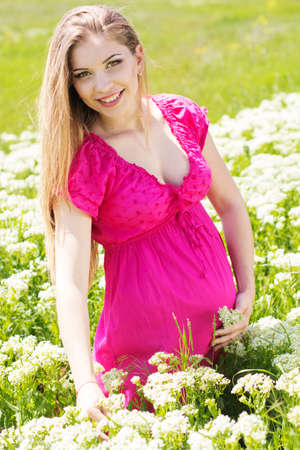 Happy pregnant woman is wearing pink dress on nature, pregnancy girl photo