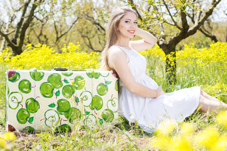 Happy pregnant woman in spring blossom garden is sitting on suitcase with apple design photo
