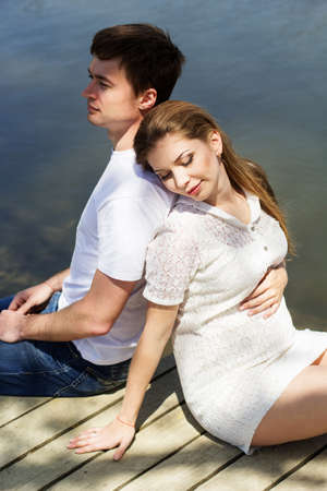 Happy young couple pregnant girl with her boyfriend are sitting on wooden bridge near blue lake, summer time, pregnancy girl photo