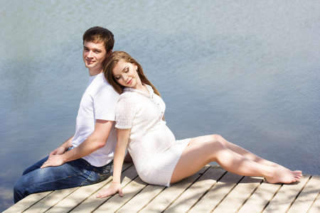 Happy young couple pregnant girl with husband are sitting on wooden bridge near blue lake, summer time, pregnancy girl photo